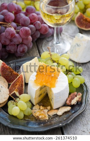 camembert with honey and fruit, snacks and wine on a plate, vertical, top view