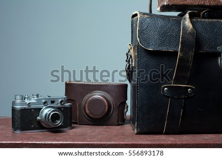 Camera and carrying case on old suitcase. Background Traveller distant countries