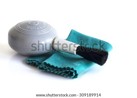 Camera cleaning set: blower brush and microfiber cloth isolated on white.