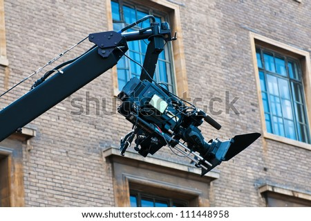 Camera crane Shooting at an outdoor location with a film camera on a crane boom arm with a brick wall in the background. - stock photo