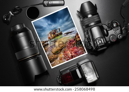 Camera equipment around a printed photo of a fisherman house - stock photo