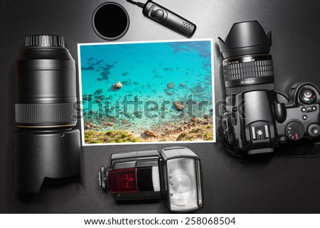 Camera equipment around a printed photo of a seascape - stock photo