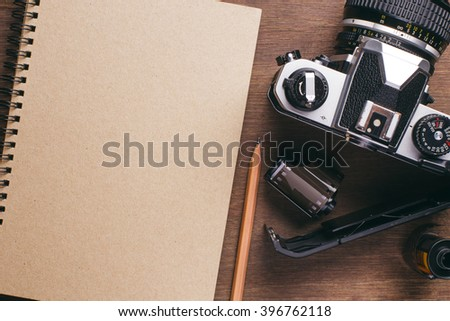 Camera, film, notebook and pencil on wooden background. Concept for photography.