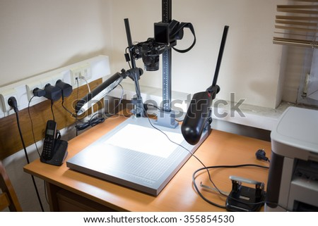Camera for photocopying is standing on the table at office.
