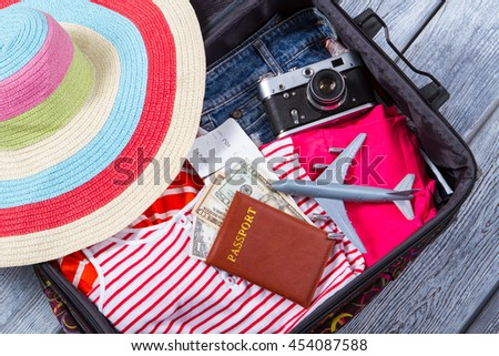 Camera in suitcase with clothes. Dollars and toy plane. Season of vacation. Everything is ready for flight. - stock photo