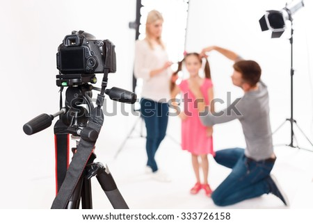 Camera is supported. Photographer leaves his camera fixed safely while helping to prepare little girl for shooting - stock photo