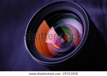 Camera lens with rainbow refraction on black background - stock photo