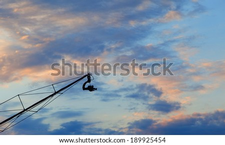 Camera on crane against the background sky - stock photo