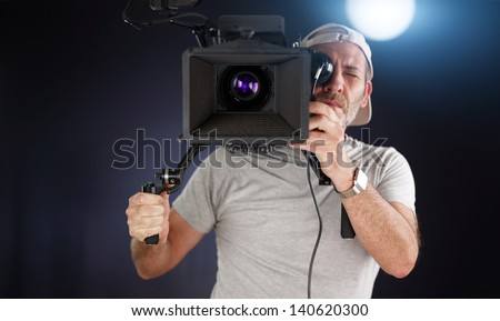 camera operator working with a cinema camera on his shoulder - stock photo