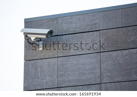 Camera system guarding blue skyscraper office building with blue sky above in horizontal format