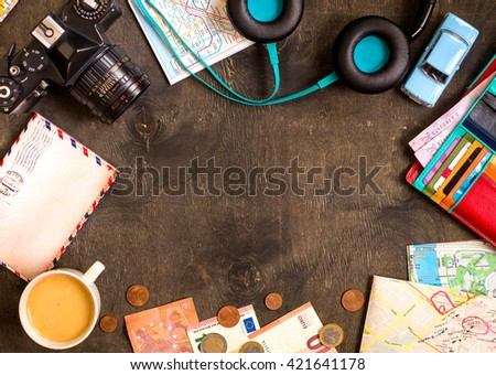 Camera, touristic maps, passport, toy car, coffee, headphones, wallet with credit cards, euro banknotes and coins on a black desk. Travel background. Tourist essentials. Plan a journey. Space for text - stock photo