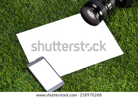 Camera with mobile phone and sheet of paper - stock photo