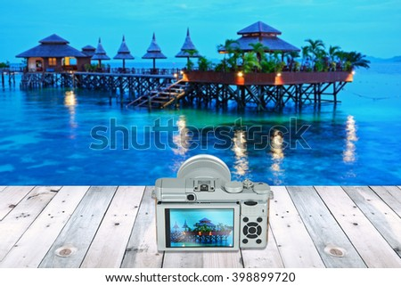 camera with screen display on wooden table with beautiful landscape in the background - stock photo
