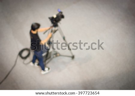 Cameraman is recording , blurred background - stock photo