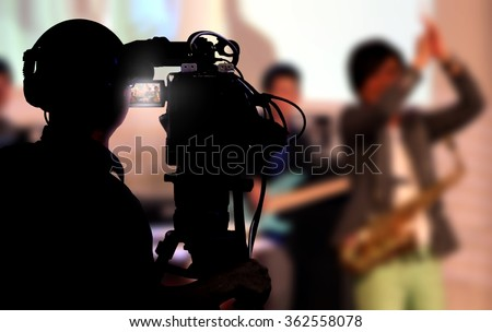 Cameraman shooting a live concert - stock photo
