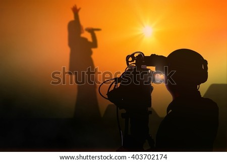 Cameraman shooting a live concert on stage - stock photo