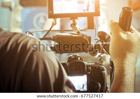 Cameraman with his video camera shooting, Hands Adjusting Camera,film production crew,behind the scenes background.