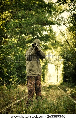 Camouflage hunter aiming with his rifle