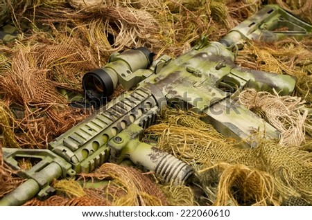 Camouflaged assault rifle and sniper suit - stock photo
