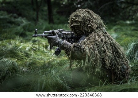 Camouflaged commando assault in forest. Soldier dressed in ghillie camouflage. - stock photo