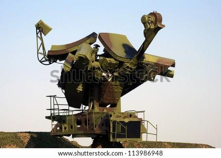 Camouflaged mobile military radar opposite blue sky - stock photo