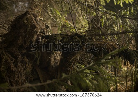 Camouflaged sniper keeps victim at gunpoint. Soldier dressed in ghillie camouflage on nature. - stock photo