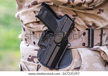 camouflaged soldier in military uniform with gun holstered to his waist