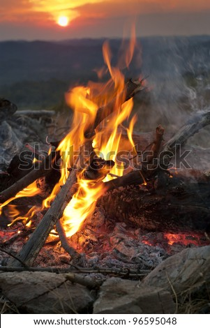 Camp bonfire in the mountains at sunset - stock photo