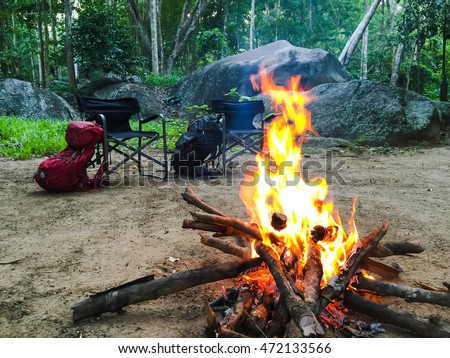 Camp Fire And Two Picnic Chairs With Two Luggage On Yard In Jungle