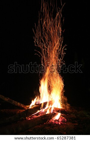 Camp fire in mountains night - stock photo