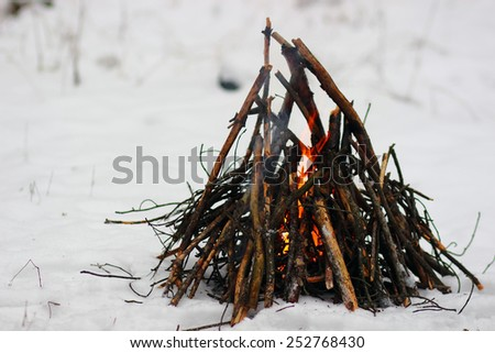 Camp fire in winter time, surrounded by snow. - stock photo