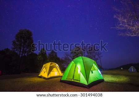 camp in forest at night with star - stock photo