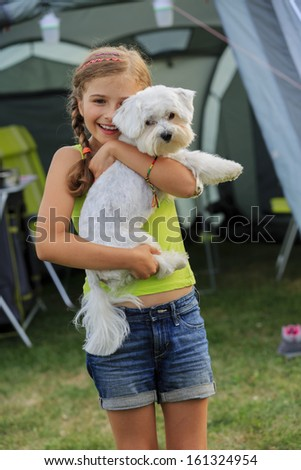 Camp in the tent - young girl playing with dog on the camping - stock photo