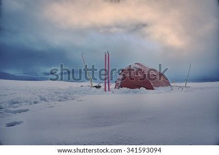 Camp in the Wintertime with Tent an skier - stock photo