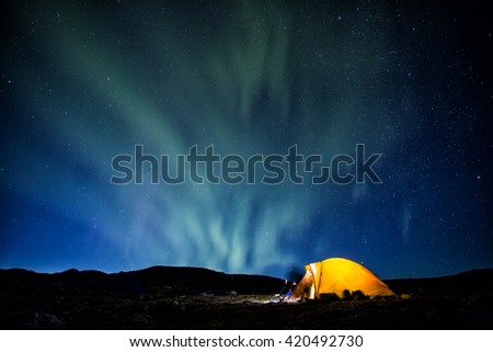 Camp, tent and Northern Lights in Lapland - Sweden - stock photo