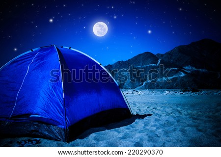 Camp tent on the beach at night, full moon glowing in dark night, summer adventure and active lifestyle concept  - stock photo