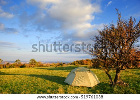 Camp tent stands in the meadow near the tree at autumn landscape background with mountains at the horizon under blue cloudy sky and light of rising sun.