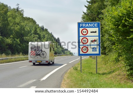 Camper passing the Sign of Speed limits at the French border - stock photo