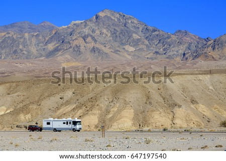 Camper taxing suv on the desert road in USA