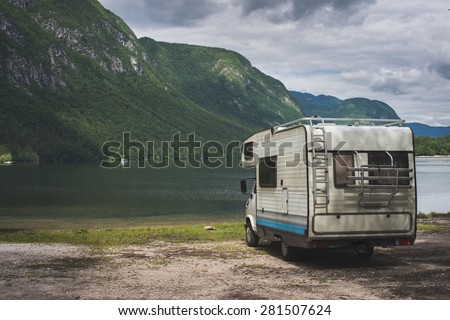 Camper van parked on a beach, mountain range landscape  - stock photo
