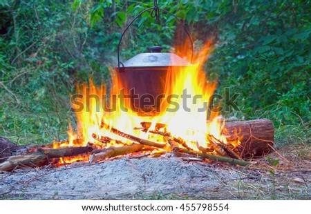 campfire background, camping, evening, adventure, cooking over an open fire - stock photo