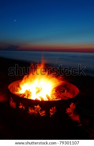 Campfire burns brightly at sunset along the beautiful beach of Lake Superior in northern Michigan - stock photo