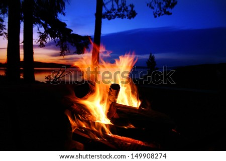 Campfire by a lake at sunset - stock photo