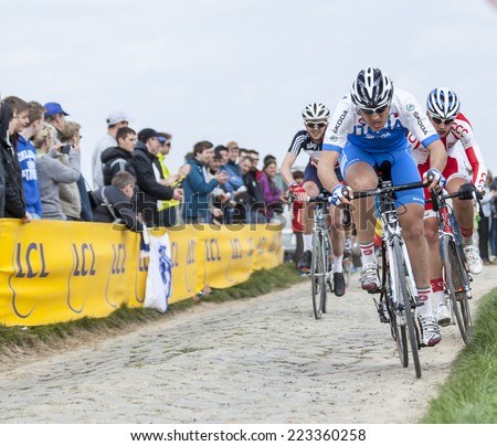 CAMPHIN EN PEVELE,FRANCE-APR 13:The peloton,containing young cyclists, riding during a race of juniors on the cobblestone sector in Camphin-en-Pevele on April 13 2014 before Paris-Roubaix cycling race - stock photo