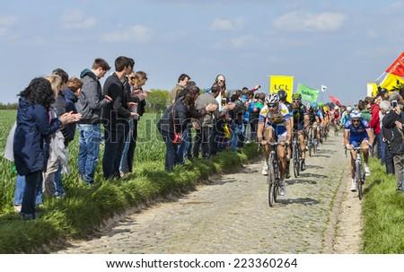 CAMPHIN EN PEVELE,FRANCE-APR 13:The peloton riding on the cobblestone sector Carrefour de l'Arbre in Camphin-en-Pevele on April 13 2014 during Paris-Roubaix cycling race - stock photo