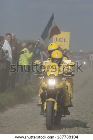 CAMPHIN EN PEVELE,FRANCE-APR 13:The yellow official bike passing in the dust on the cobblestone sector Carrefour de l'Arbre in Camphin-en-Pevele town on April 13 2014 during Paris-Roubaix cycling race
