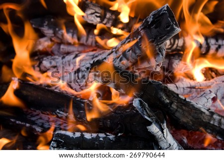 Camping bonfire with flame and firewood fragment close-up view in the dark - stock photo