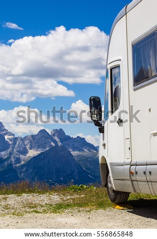 Camping car in the mountains, people travel in Italian Alps