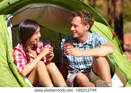 Camping couple drinking water in tent smiling happy outdoors in forest enjoying sun at looking at view. Happy multiracial couple relaxing after outdoor activity hiking. Asian woman, Caucasian man. - stock photo
