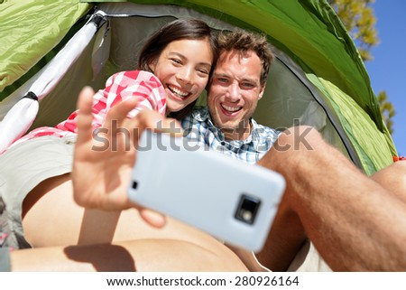 Camping couple in tent taking selfie using smartphone. Campers self portrait photo picture. Woman and man smiling happy outdoors in forest. Happy people having fun. Asian woman, Caucasian man. - stock photo
